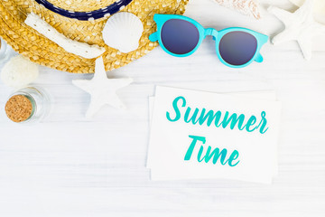 Wall Mural - Blue summer time word on white card at wood table with sunglasses,straw hat,starfish,glass bottle top view,Vacation concept.
