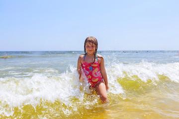 happy girl on a tropical beach ocean has fun with splash