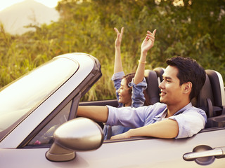 young asian couple riding in a convertible car