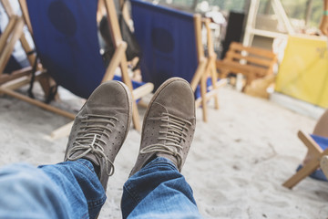 Men feet in sneakers on background of deckchairs on beach