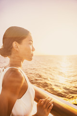 Wall Mural - Cruise luxury travel elegant woman enjoying sunset view from balcony suite deck. Europe destination vacation holiday Asian beauty relaxing.