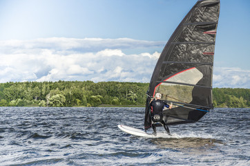 The man on the board for windsurfing. Recreational Water Sports. Windsurfing. Extreme Sport Action. Healthy Active Lifestyle.