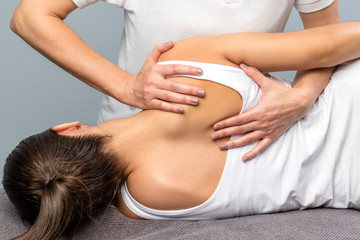 Detail of female therapist manipulating shoulder blade on patient.