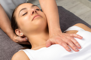 Female physiotherapist manipulating neck and chest of patient.