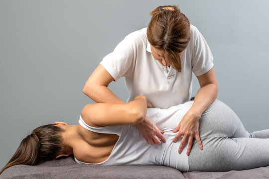Female therapist doing osteopathic spine treatment on patient.