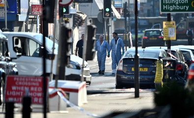 Police forensic officers walk down a road close to where a vehicle collided with pedestrians in the Finsbury Park neighbourhood of North London