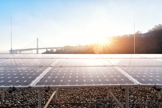 solar panels near modern suspension bridge with sunbeam