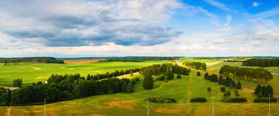 In de dag Lime groen Panoramic summer rural landscape. Green fields, meadows, trees, road and blue sky with clouds. Minsk region, Belarus.