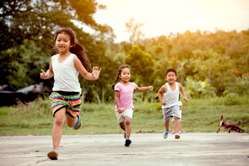 Asian children having fun to run and play together in the field in vintage color tone