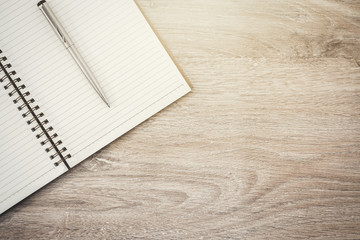 Blank notebook and pen on wood background