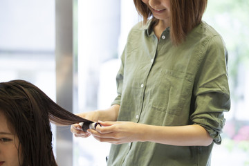 Hairdresser is wearing a rod for a long hair of a woman