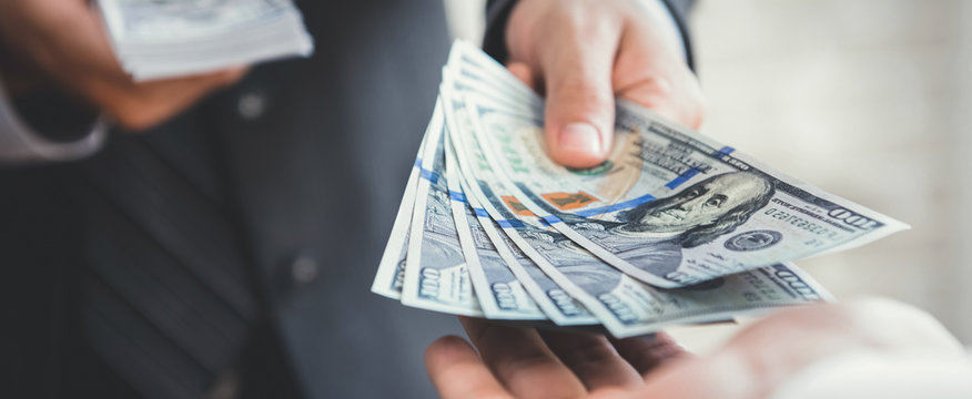Businessman giving or paying money, US dollar bills