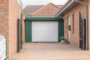 Grüne Garage mit weißem Tor