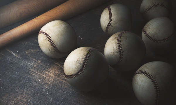 Numerous balls and bats on wooden table