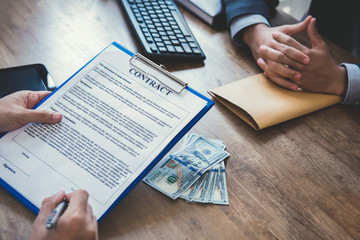 Business partner making contract with money on the table