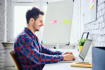 Web designer, hipster working on laptop in office
