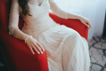 Young beautiful bride sitting on armchair and waiting for her groom