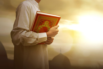 Muslim man in traditional dress holding holy book Koran