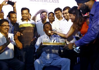 A fan offers a piece of cake to legendary Brazilian soccer player Pele as they celebrate his upcoming birth anniversary at a promotional event in Kolkata