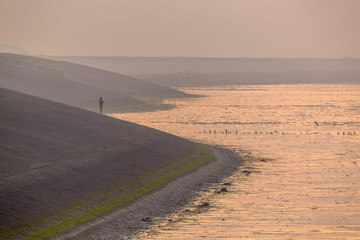 Wall Mural - Person watching sunset from Sea dike in orange haze