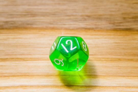 A translucent green twelve sided playing dice on a wooden background with number twelve on a top