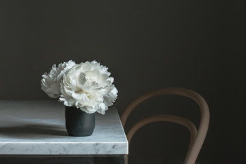 white peonies on marble table with wooden chair
