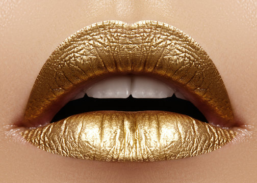 Beautiful closeup with female plump lips with gold color makeup. Fashion celebrate make-up, glitter cosmetic