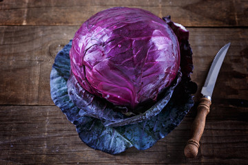 Red cabbage and knife over rustic wooden background