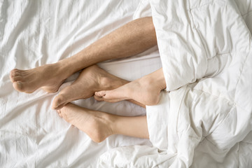 Legs of lovers under blanket
