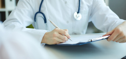 Female medicine doctor hand holding silver pen writing something on clipboard closeup. Ward round, patient visit check, medical calculation and statistics concept. Physician ready to examine patient
