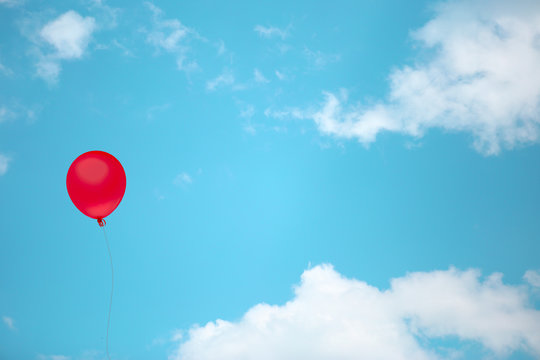 Red balloon on vintage sky