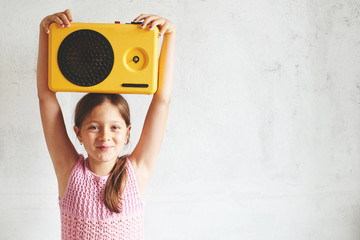 Little girl on a white background holds a retro tape recorder