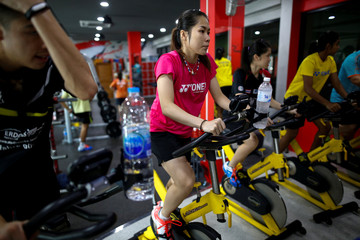Thailand's badminton player Ratchanok Intanon, who hopes to win gold at the Rio Olympics, rides a fitness bike during a training session at a gym in Bangkok