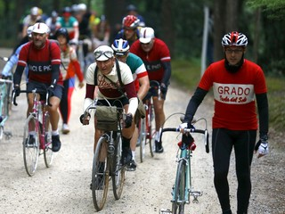 """Cyclists ride vintage bicycles on gravel roads during the Strade Bianche section of the """"Eroica"""" cycling race for old bikes in Gaiole in Chianti"""