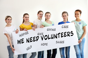 Group of teens holding poster with text WE NEED VOLUNTEERS on color background