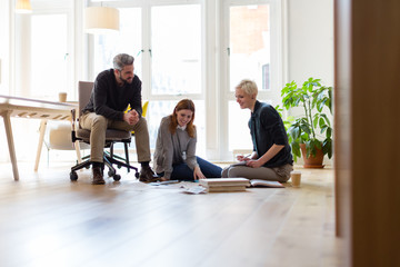 Group of designers discussing ideas with paperwork on office floor