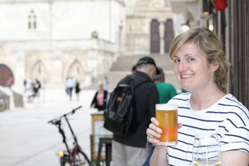 Happy and funny woman holding her cold refreshing beer