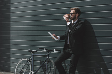 stylish businessman with bicycle using digital tablet and drinking coffee while standing in front of black wall