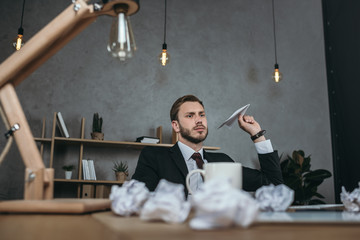 young businessman throwing paper airplane while sitting at workplace