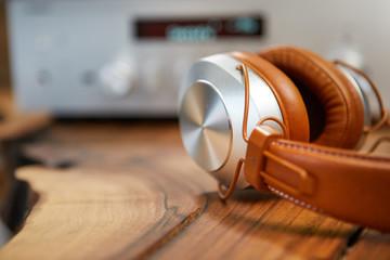 Vintage Headphones lie on a wooden table. Background amplifier hifi