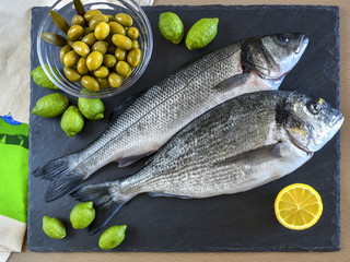 Two ready to cook raw fish with lemon and olives on stone slate board.