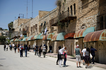 "Visitors on a tour held by leftwing NGO ""Breaking the Silence"" walk down Shuhada street in the West Bank city of Hebron"