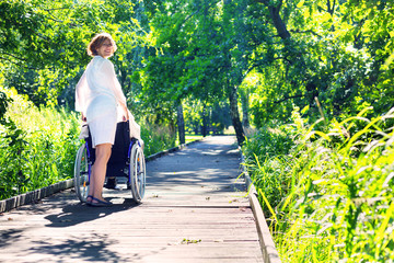 woman pushing on wheelchair in the park