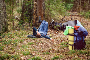 Man lying on grass near his backpack in a forest. A person rests after a long journey. Consolidated way of life and recreation in nature.