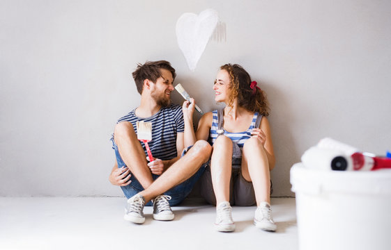 Young couple in love painting walls in their new home.