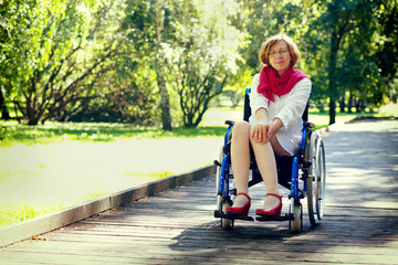 young adult woman on wheelchair in the park