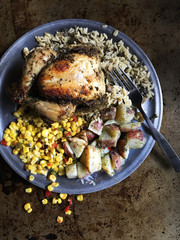 baked chicken dinner with wild rice, corn, red potato sides