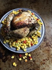 roasted chicken on bed of colorful corn in rustic setting