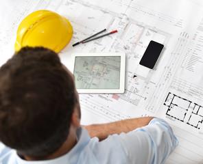Planung Hausbau - Architekt am Schreibtisch mit modernen Arbeitsgeräten vor einer technischen Zeichnung/ Grundriss Neubau Haus