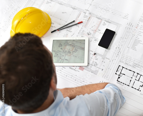 planung hausbau architekt am schreibtisch mit modernen arbeitsger ten vor einer technischen. Black Bedroom Furniture Sets. Home Design Ideas